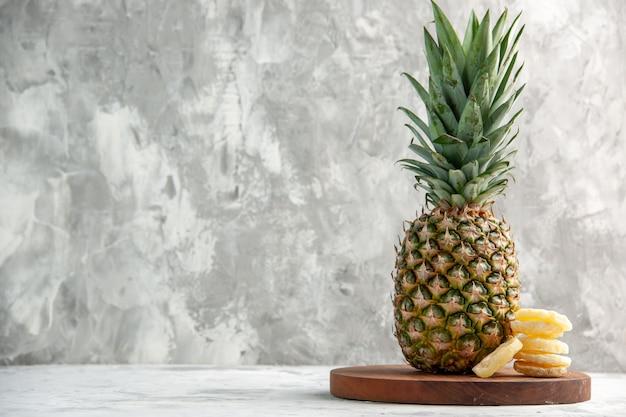 Vista frontale dell'intero ananas dorato fresco e lime sul tagliere in piedi su una superficie di marmo