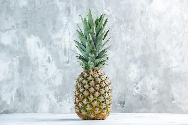 Vista frontale dell'intero ananas dorato fresco in piedi su una superficie di marmo