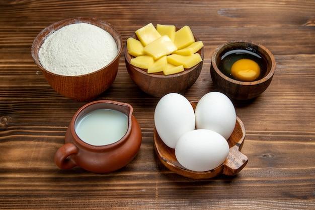 Uova crude intere di vista frontale con farina di formaggio e latte sulla pasticceria della pasta dell'uovo del prodotto della tavola di legno marrone
