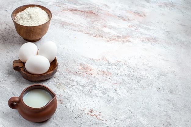 Vista frontale intere uova crude con farina e latte su sfondo bianco chiaro cibo crudo prima colazione a base di uova