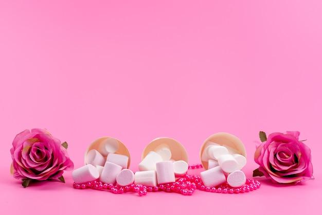 Una vista frontale whtie marshmallow all'interno di pacchetti di carta insieme a rose rosa isolate sulla scrivania rosa, dolciumi di zucchero