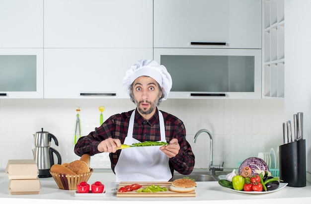 Front view of wide-eyed cook holding knife cutting vegetables in the kitchen
