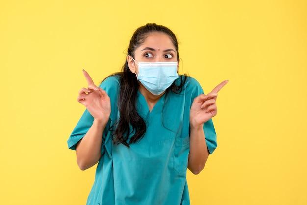Вид спереди широко раскрытыми глазами женщина-врач, стоящая на желтом фоне