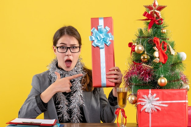 Front view wide-eyed girl with eyeglasses sitting at the table showing gift xmas tree and gifts cocktail