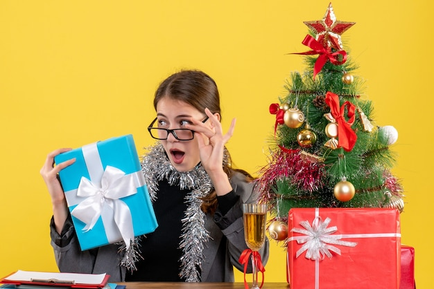 Front view wide-eyed girl with eyeglasses sitting at the table taking off eyeglasses xmas tree and gifts cocktail
