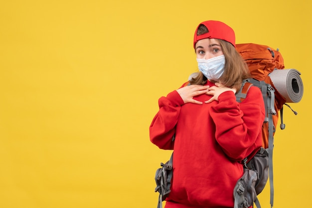 彼女の胸に手を置いてバックパックとマスクを持つ正面図の目を丸くしたヒッチハイカーの女の子