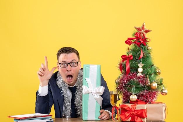 Vista frontale dell'uomo con gli occhi spalancati che punta verso l'alto seduto al tavolo vicino all'albero di natale e regali sul giallo