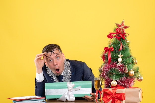Front view of wide-eyed man taking off eyeglasses sitting at the table near xmas tree and presents on yellow