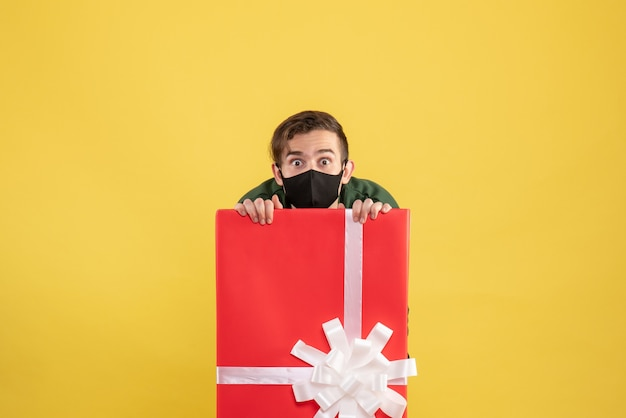 Front view wide-eyed man with mask hiding behind big giftbox on yellow