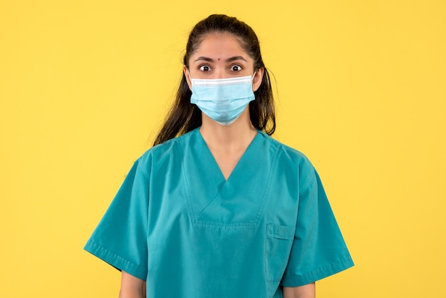 Front view wide-eyed pretty female doctor with medical mask on yellow background