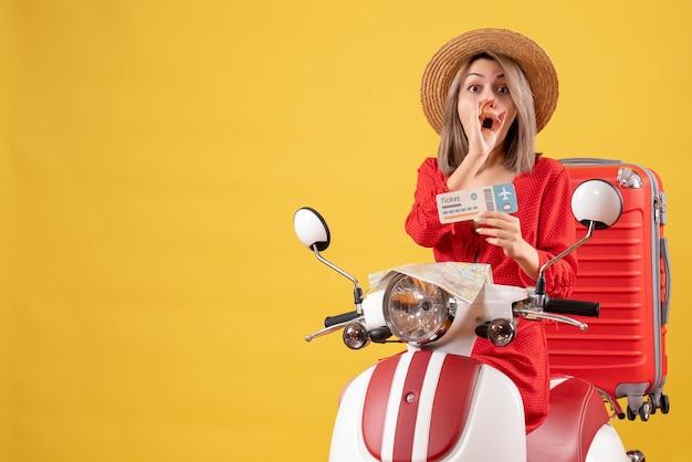 Vista frontale giovane donna con gli occhi spalancati in vestito rosso che tiene il biglietto sul motorino