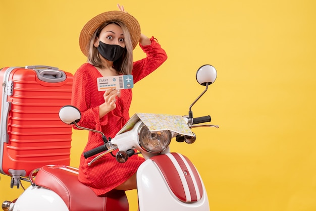 Vista frontale giovane donna con gli occhi spalancati con maschera nera su ciclomotore con valigia rossa che tiene biglietto