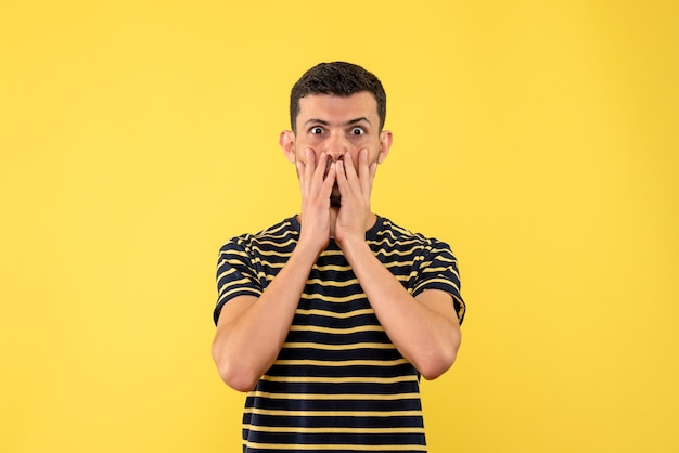 Front view wide-eyed young man in black and white striped t-shirt yellow isolated background