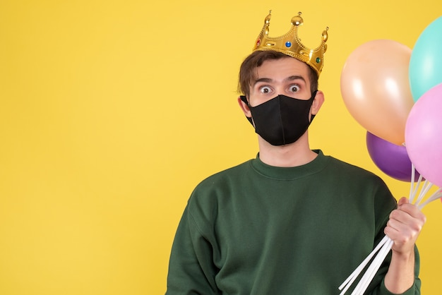 Front view wide-eyed young man with crown and black mask holding balloons on yellow