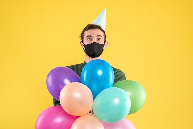 黄色の上に立っているパーティーキャップとカラフルな風船と正面図目を大きく見開いた若い男