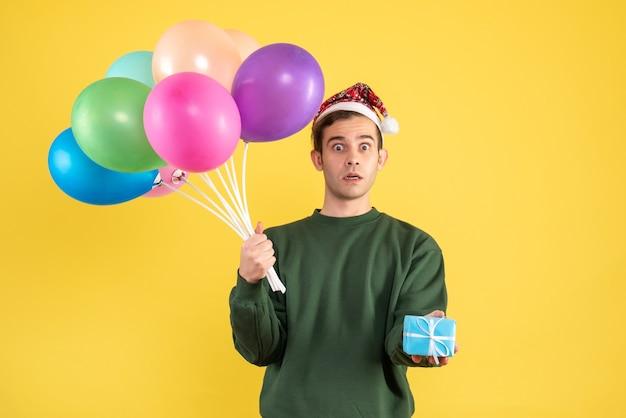 Вид спереди широкоглазого молодого человека в новогодней шапке и разноцветных воздушных шарах, держащего синюю подарочную коробку на желтом