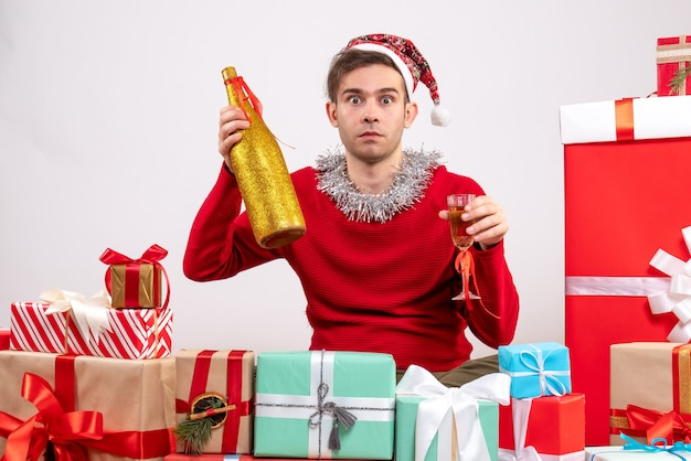 Front view wide-eyed young man with santa hat holding champagne sitting around xmas gifts