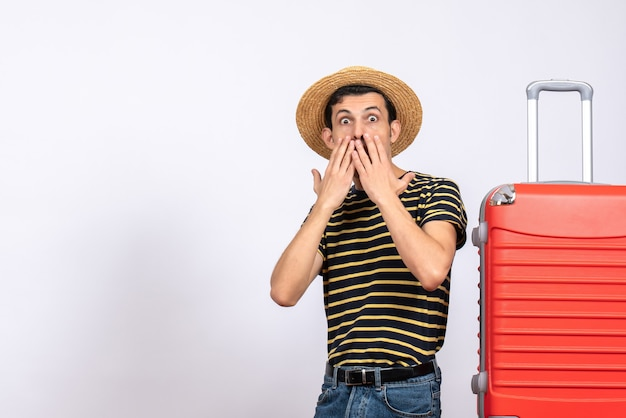 Front view wide-eyed young man with straw hat standing near red suitcase