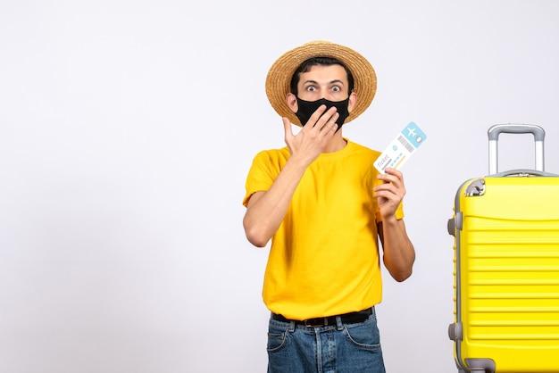 旅行チケットを保持している黄色のスーツケースの近くに立っている麦わら帽子と正面図目を大きく見開いた若い男