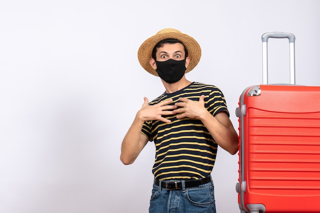 Front view wide-eyed young tourist with black mask standing near red suitcase pointing at himself