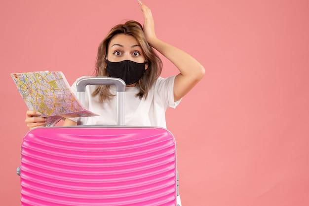 Vista frontale giovane donna con gli occhi spalancati con maschera nera che tiene mappa in piedi dietro la valigia rosa pink