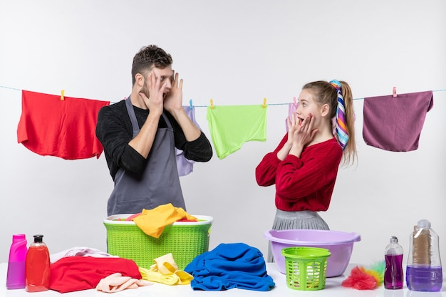 Front view of wife and husband looking at each other putting hands on their faces standing behind table laundry baskets and washing stuffs on table clothes on rope