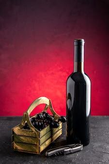 Vista frontale bottiglia di vino uva nera in scatola di legno apribottiglie su sfondo rosso chiaro