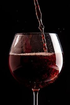 Bicchiere da vino vista frontale che viene versato con vino rosso su bevanda alcolica di natale champagne di colore nero black
