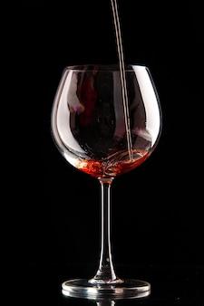 Bicchiere da vino vista frontale che viene versato con vino rosso su alcol di natale champagne di colore nero
