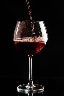 Bicchiere da vino vista frontale che viene versato con vino rosso su colore nero bere champagne natale alcol