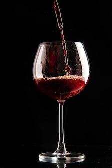 Bicchiere da vino vista frontale che viene versato con vino rosso su champagne xmas di colore nero