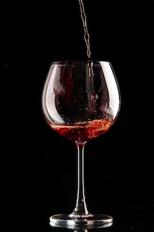 黒い色のドリンク シャンパン アルコールに赤ワインを注ぐ正面のワイン グラス