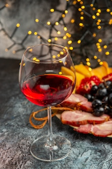 Front view wine glass grapes cheese pieces meat slices on wood plate on dark background