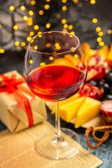 Vista frontale bicchiere di vino uva pezzi di formaggio fette di carne su piatto di legno su luci di natale scure