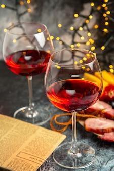 Vista frontale bicchiere di vino uva pezzi di formaggio fette di carne su piatto di legno giornale su luci di natale scure