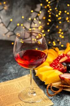 Vista frontale bicchiere di vino uva pezzi di formaggio fette di carne su piatto di legno giornale su luci di natale scure dark