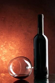 Bicchiere da vino vista frontale con bottiglia di vino su bevanda alcolica di natale champagne di colore scuro