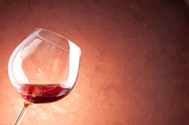 Bicchiere da vino vista frontale con poco vino all'interno su bevanda alcolica di natale champagne di colore scuro