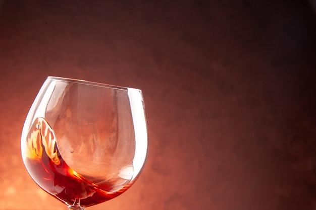 Бокал для вина с небольшим количеством вина внутри на темном шампанском, рождественский алкогольный напиток, вид спереди