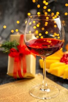 Regalo di natale di vetro di vino vista frontale su sfondo scuro