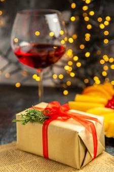 Regalo di natale di vetro di vino vista frontale su luci di natale scure