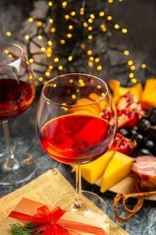 Vista frontale bicchieri da vino uva pezzi di formaggio fette di carne su piatto di legno su luci di natale scure