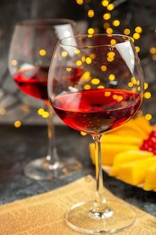 Bicchieri da vino vista frontale regalo di natale sul giornale su luci di natale scure