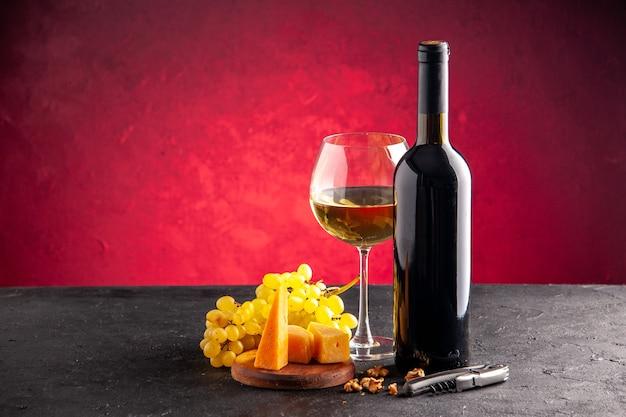 Вид спереди вино в стеклянной бутылке для вина, желтый виноград, сыр на деревянной доске, открывалка для вина на темном столе, светло-красном фоне
