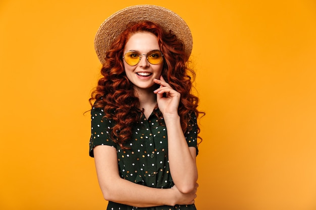 Front view of winsome ginger woman. attractive caucasian girl smiling on yellow background.
