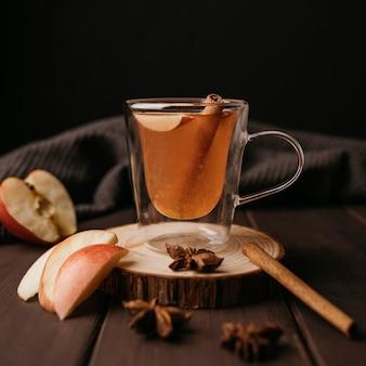 Зимний горячий напиток в стакане с яблоком и корицей, вид спереди