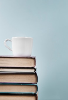 Front view with mug on books with copy space