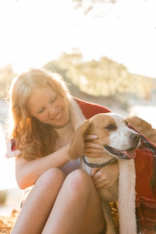 Вид спереди женщина и собака, завернутые в одеяло