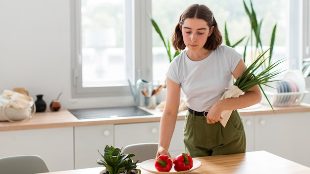 Front view woman arranging vegetables at home