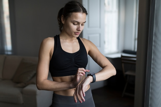Front view of woman in athleisure looking at her smartwatch